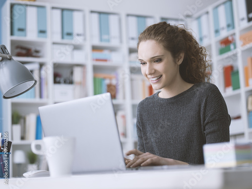Smiling student girl connecting with a laptop