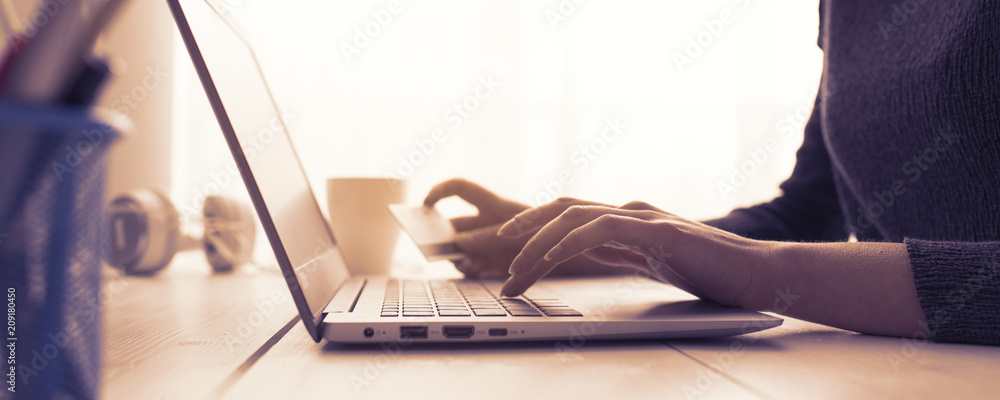 Fototapeta Woman doing online shopping with a credit card