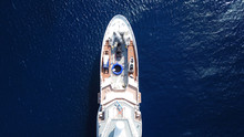 Aerial Drone Bird's Eye View Photo Of Luxury Yacht With Wooden Deck Docked In Ocean Deep Blue Waters