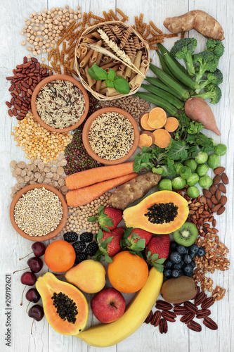 Poster Assortiment Healthy high fibre food with grains, legumes, whole wheat pasta, fresh fruit, vegetables, nuts, seeds and cereals. Top view on rustic background.