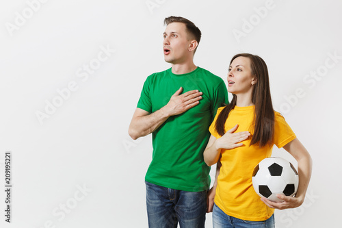 Photo Emotional couple, woman man, football fans in yellow green t-shirt cheer up support team with soccer ball singing national country anthem isolated on white background