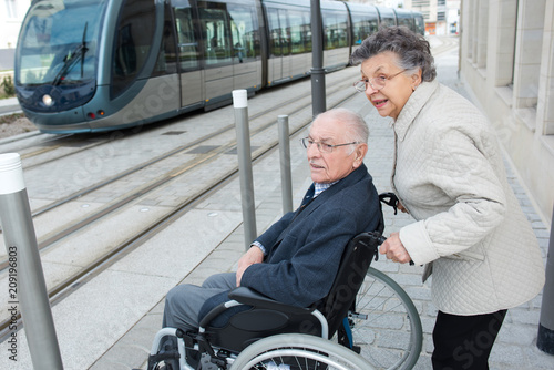 man with disease on a wheelchair and his lovely woman