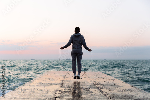 Photo  Young sportsman jumping with skipping rope, spending workout on pier, looking at seaside