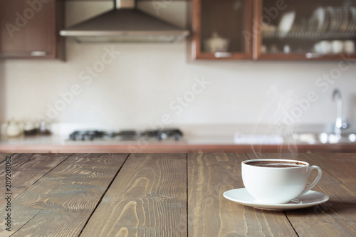 Cup of black coffee on wooden tabletop in blurred modern kitchen. Copy space. Indoor.