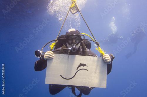 Foto op Canvas Duiken Taucher mit Ausrüstung Unterwasser im Meer guckt zum Betrachter