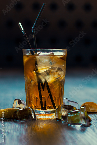 Photo  Delicious alcoholic cocktail with lemon and lime, pieces of ice on a wooden back