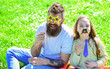 canvas print picture - Best friends concept. Dad and daughter sits on grass at grassplot, green background. Child and father posing with eyeglases, mustache and tie photo booth attributes. Family spend leisure outdoors.