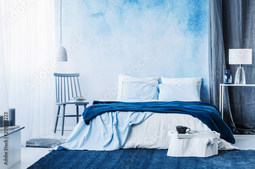 Fotobehang Sportwinkel Navy blue carpet in minimal bedroom interior with blanket on bed next to a chair and under a lamp