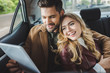 smiling young couple using digital tablet while sitting together in car
