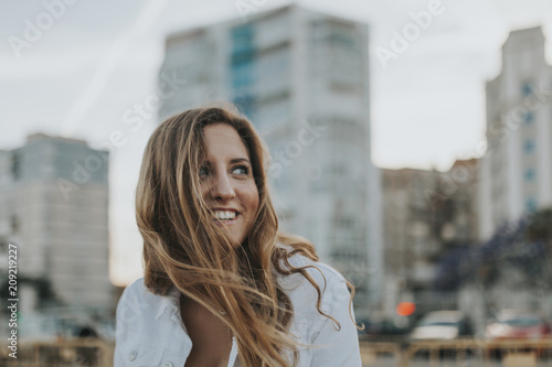 Happy smiling blonde woman portrait, with buildings and the city streets in the background at sunset.