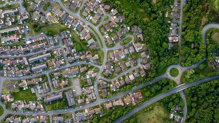 Top down aerial view of an urban area in a small town surrounded by trees and greenery