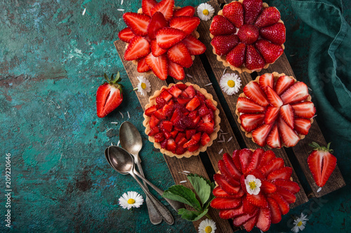 strawberry tartlets on green background
