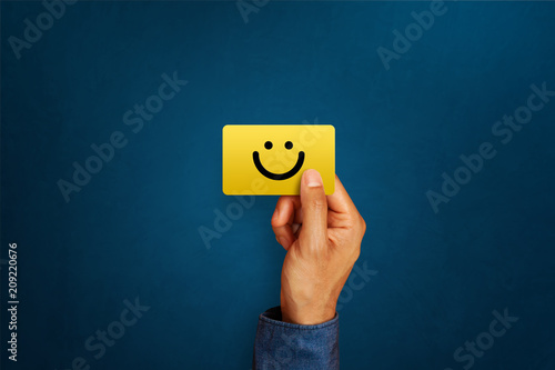 Fotografía  Hand of client show a feedback with smiley face card