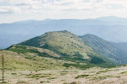 Fotobehang Blauwe hemel Mountains hills landscape green clouds
