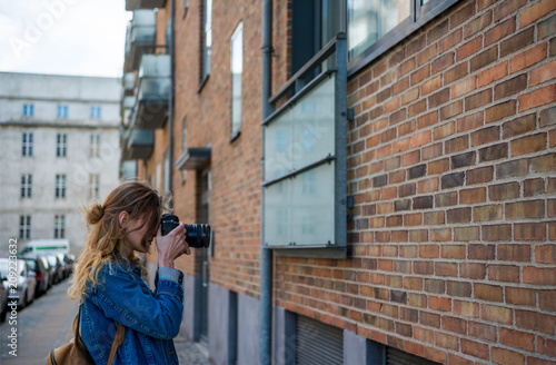 woman with photo camera taking picture of architecture in copenhagen, denmark Poster