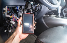 Diagnosis Of Car Faults: A Portable Auto Scanner With OBD2 Interface In The Electrician's Hand. On The Background Of The Interior Of The Car With A Dismantled Panel And Wires.