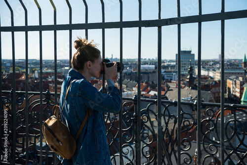 selective focus of young woman taking picture of copenhagen city, denmark Poster