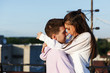Girl kisses her man standing on the roof and watching the sunset