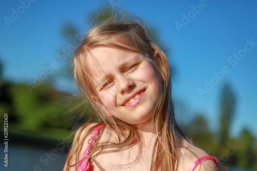 Fotografie, Obraz  Ein Schulmädchen mit zerzaustem Haar lächelt in die Kamera