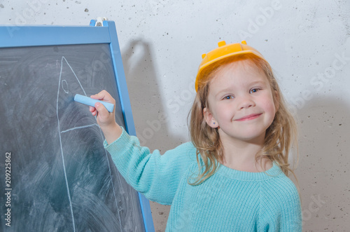 Fototapeta girl in a helmet paint a house on a chalk Board