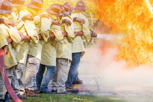 In de dag Vuur Firemen using water from hose for fire fighting at fire fight training of insurance group.Firefighter wearing a fire suit for safety under the danger training case.