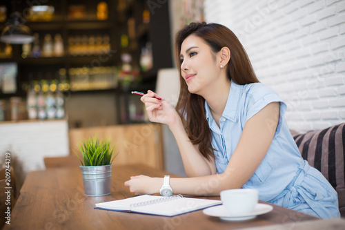 Fototapeta Young business woman sitting at table in cafe and writing in notebook and cup of coffee. Freelancer working in coffee shop. obraz na płótnie