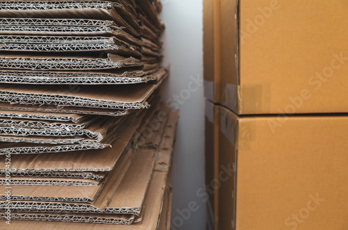 Foto  Old corrugated cardboard boxes stacked close to new brown carton boxes stacked