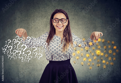 Photo Happy young woman with many questions and answers ideas light bulbs