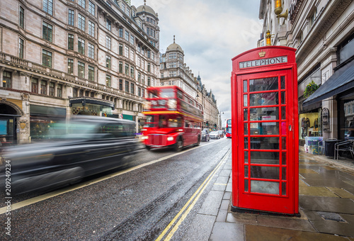 Fotobehang Londen rode bus London, England - Iconic blurred black londoner taxi and vintage red double-decker bus on the move with traditional red telephone box in the center of London at daytime