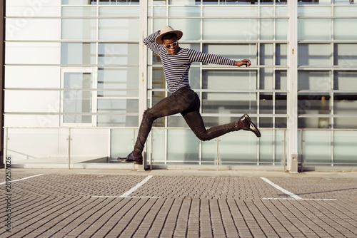 Stylish black man jumping on street