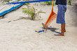 An employee is cleaning the beach. Rake for a tool to get hay from the sea and garbage disposal from the beach. White sandy beach.