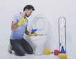 Young man unclogging toilet with plunger.