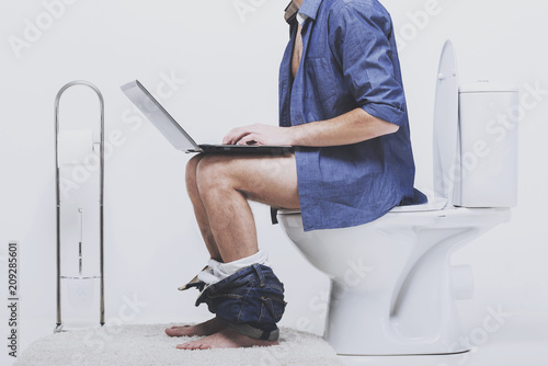 Obraz na plátně Man is working with laptop while sitting on toilet.