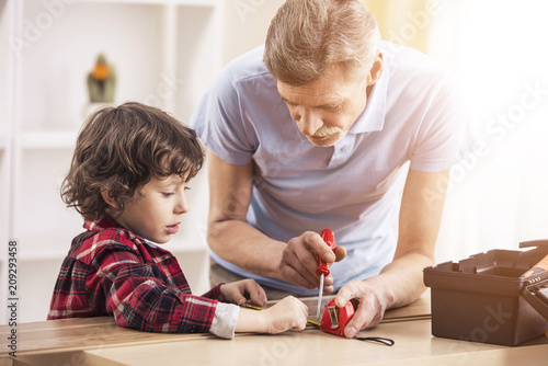 Little baby grandson and his grandfather works with screwdriver. Fototapeta