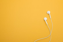 White Earphones On Yellow Background With Copy Space
