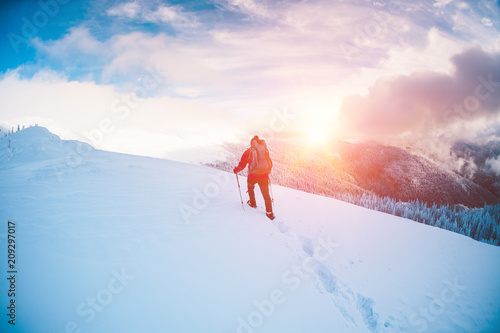 A man in snowshoes in the mountains. Wallpaper Mural