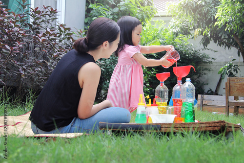 Fotografie, Obraz  Asian mom and little daughter experiment with different water colors mixing for learning and strengthen Imagine