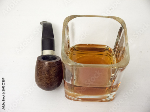 Photo  Briar smoking pipe near a glass of whisky close view with white background