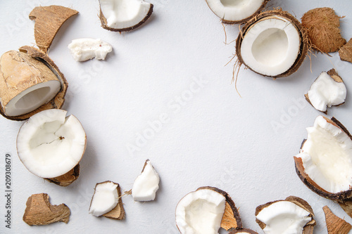 Cracked coconut on gray background with copy space. Food or cosmetics ingredient © Asya