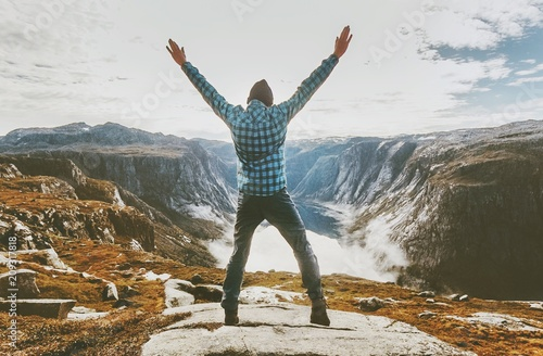 Fotografia  Traveler man exploring mountains alone happy raised hands adventure journey summ