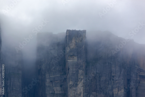 Fotomural View of Preikestolen steep cliff in fog from the Lysefjorden, Rogaland, Norway