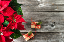 Holiday Gifts And Christmas Poinsettia Flower, Traditional Decoration On Wooden Table