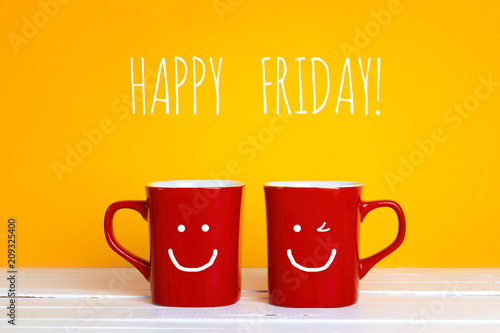 Photographie  Two red coffee mugs with a smiling faces on a yellow background with with the phrase Happy friday
