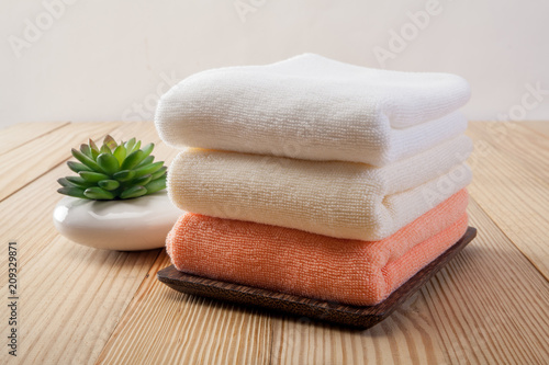Valokuvatapetti Stack of bath towels with lavender flowers on light wooden background closeup