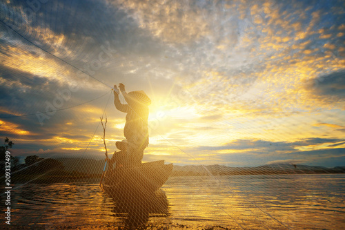 Obraz Fishermen using nets to catch fish at the Bangpra lake during sunrise time. - fototapety do salonu