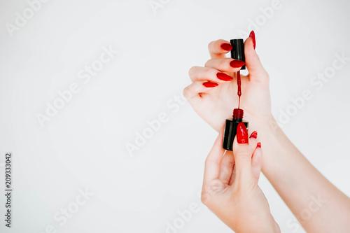 Fototapeta Beautiful girl showing red manicure nails