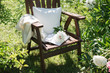 a wooden chair in the garden and book with pion