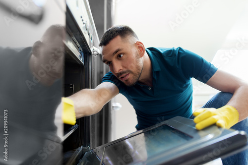 Obraz household and people concept - man wiping table with cloth cleaning inside oven at home kitchen - fototapety do salonu