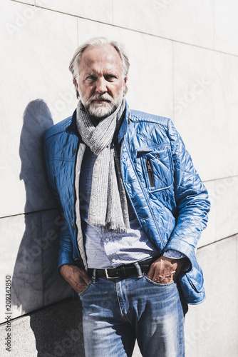 Foto op Aluminium Wand Portrait of fashionable mature man leaning against a wall