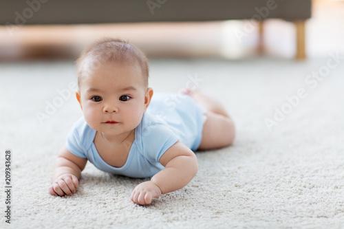 Fototapeta babyhood, childhood and people concept - sweet little asian baby boy lying on floor obraz